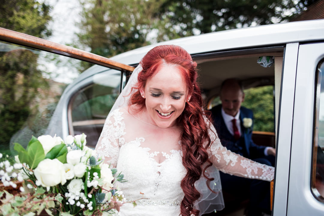 Red haired bride getting out of wedding car