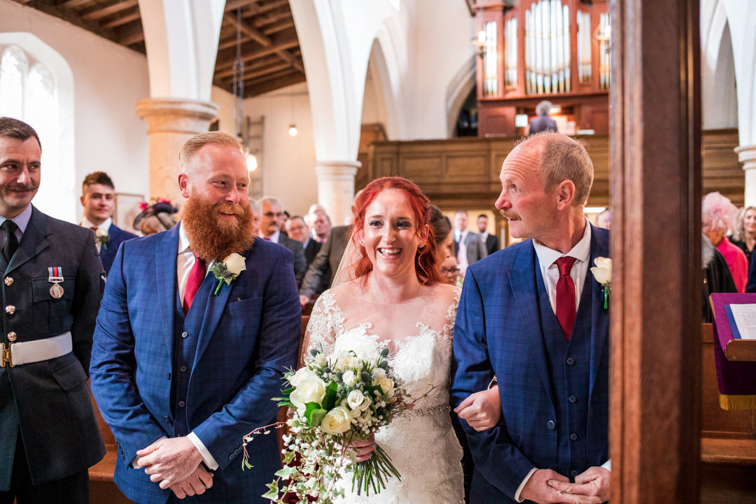 Red haired bride with father walking down the aisle in church