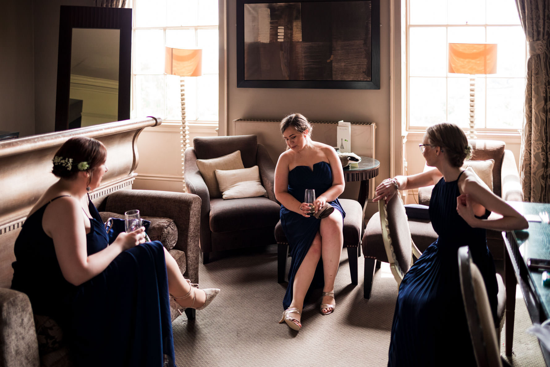 Bridesmaids in dark blue dresses in hotel room