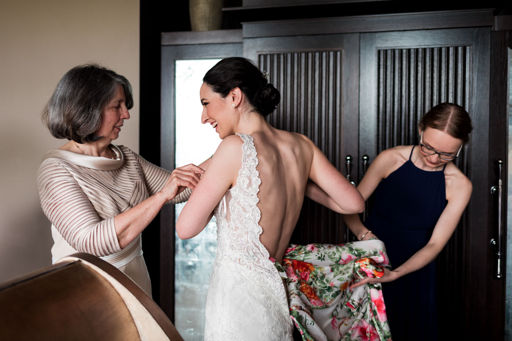 Mother of the bride helping bride to put on wedding dress