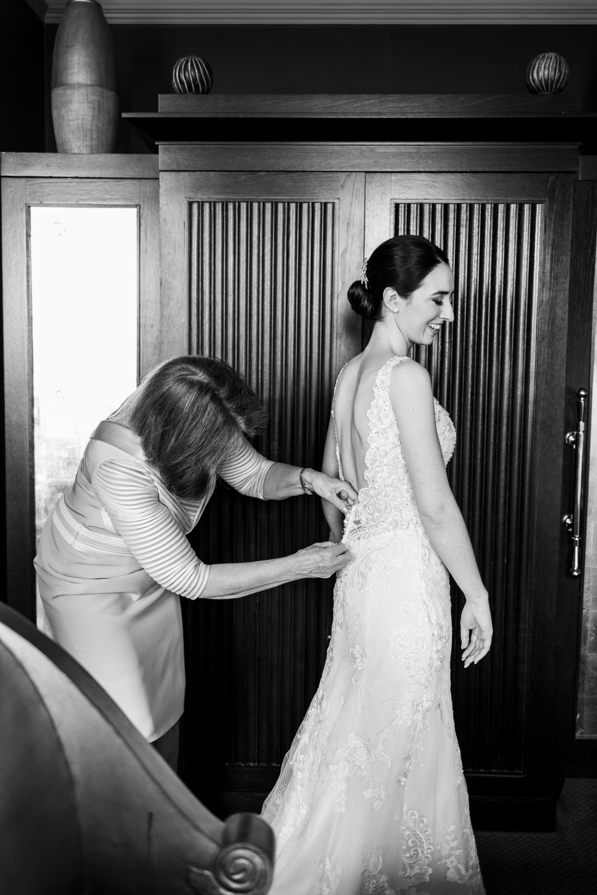 mother of the bride fastening buttons on wedding dress in black and white