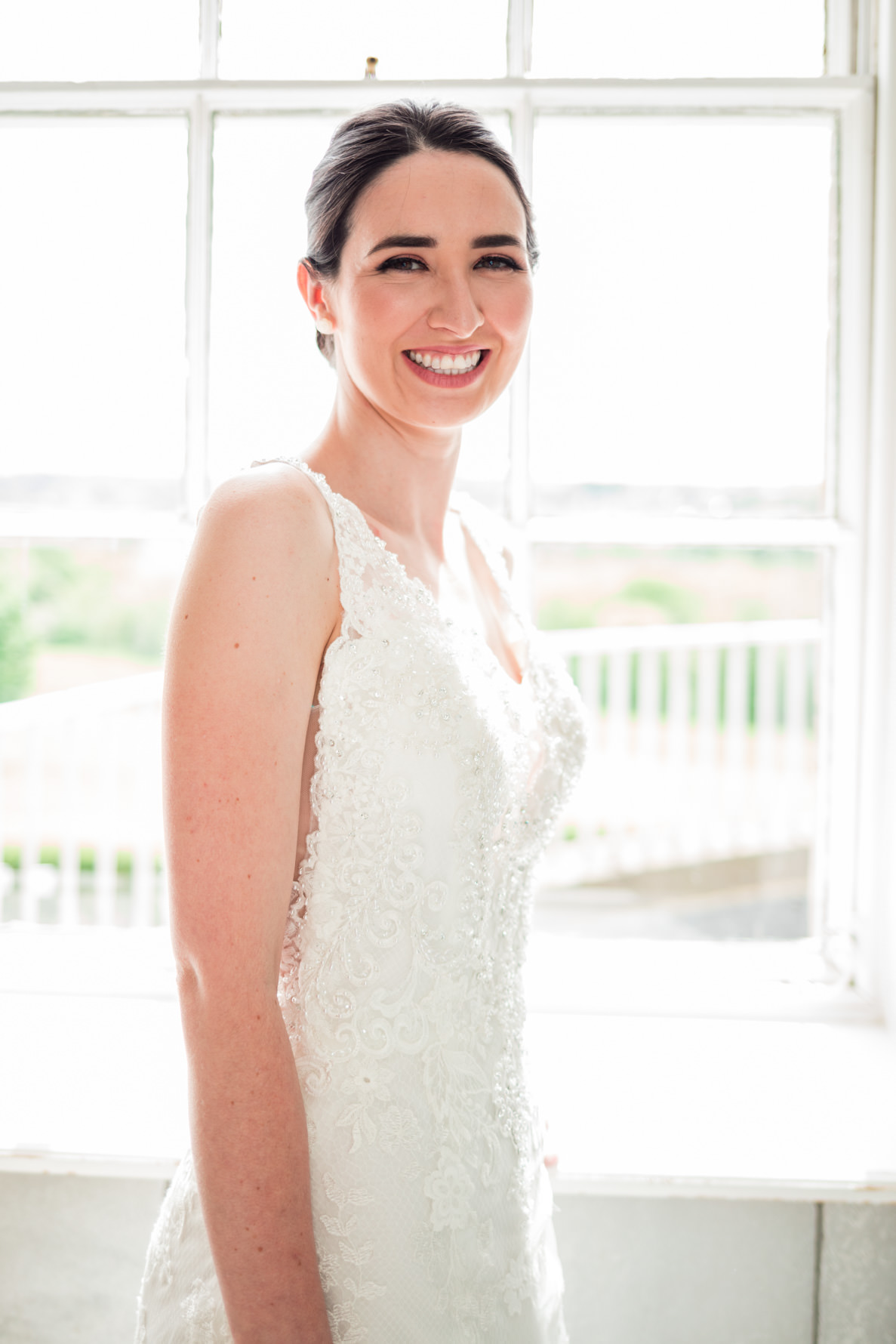 dark haired bride smiling in front of big window
