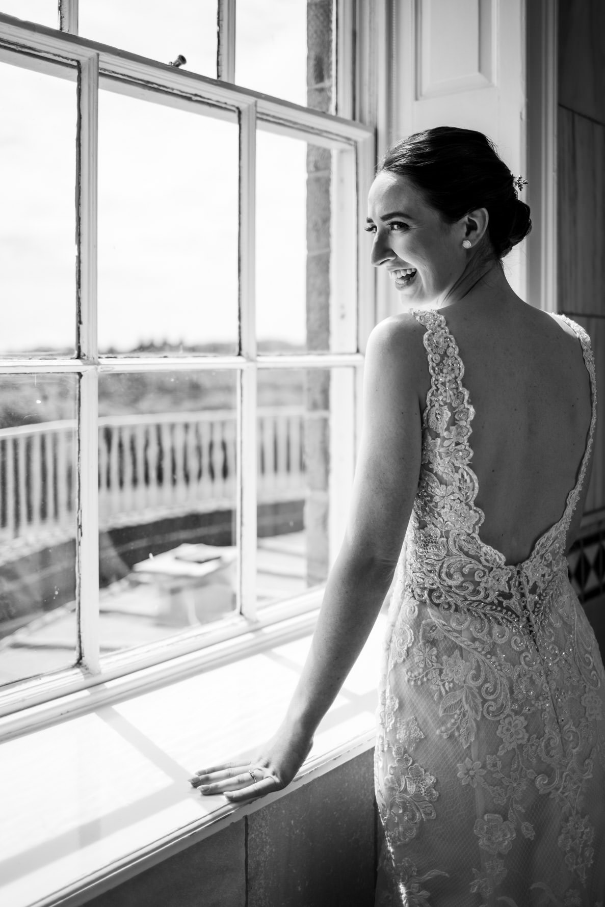 dark haired bride looking back over shoulder smiling in front of big window