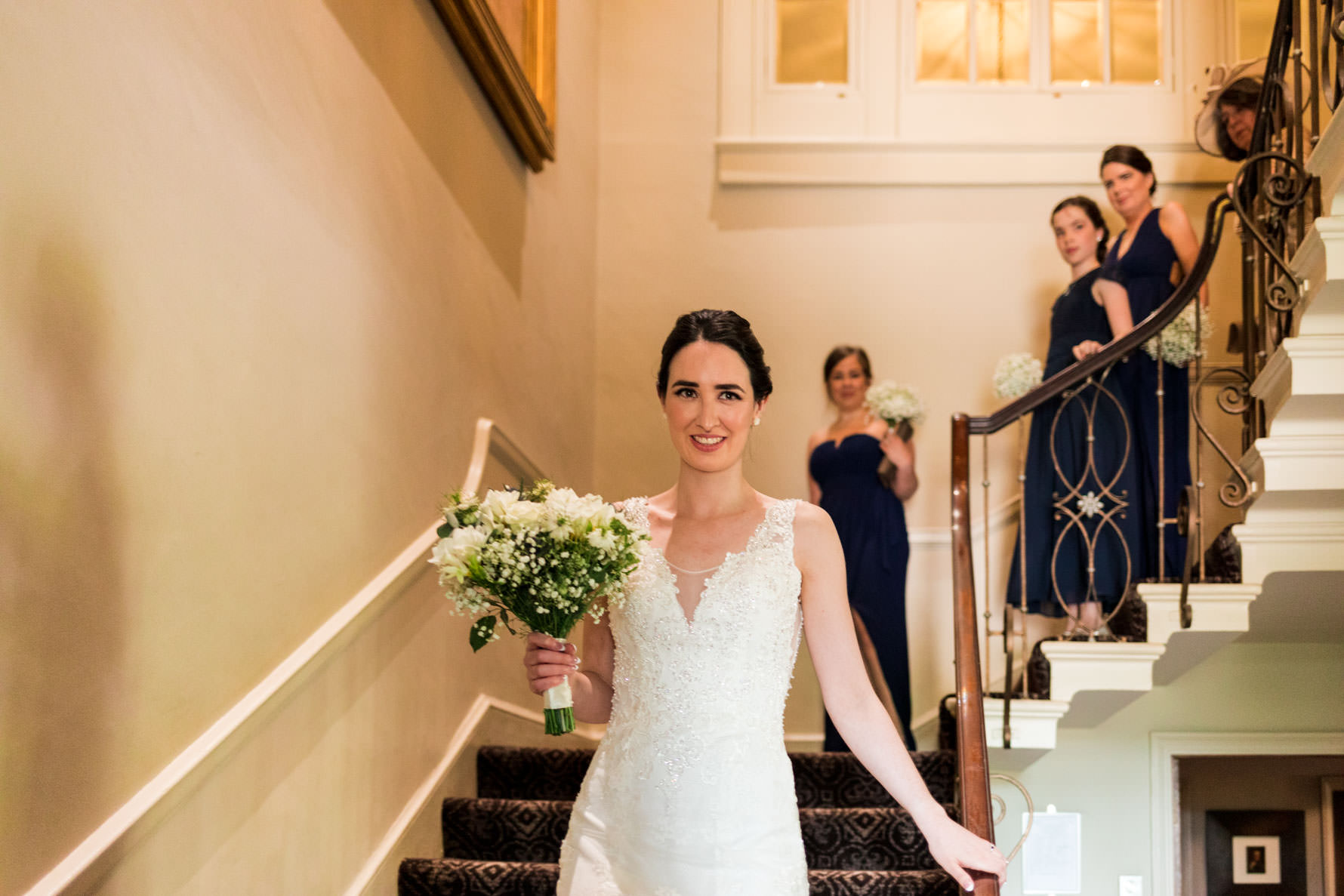 bride walking down staircase with bridesmaids following behind