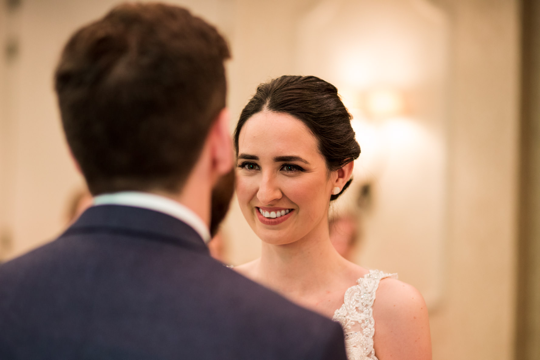 Dark haired bride smiling at groom during wedding ceremony