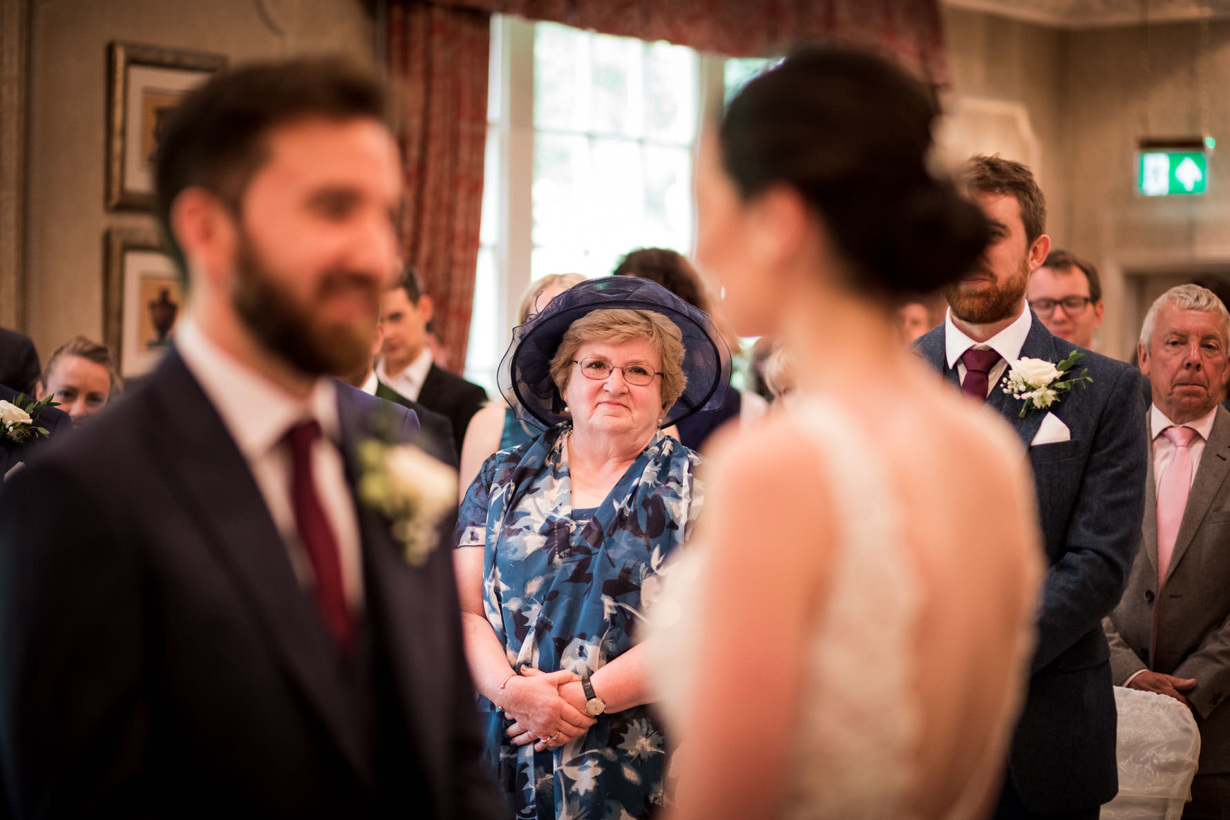mother of groom looking emotional at bride and groom during wedding ceremony