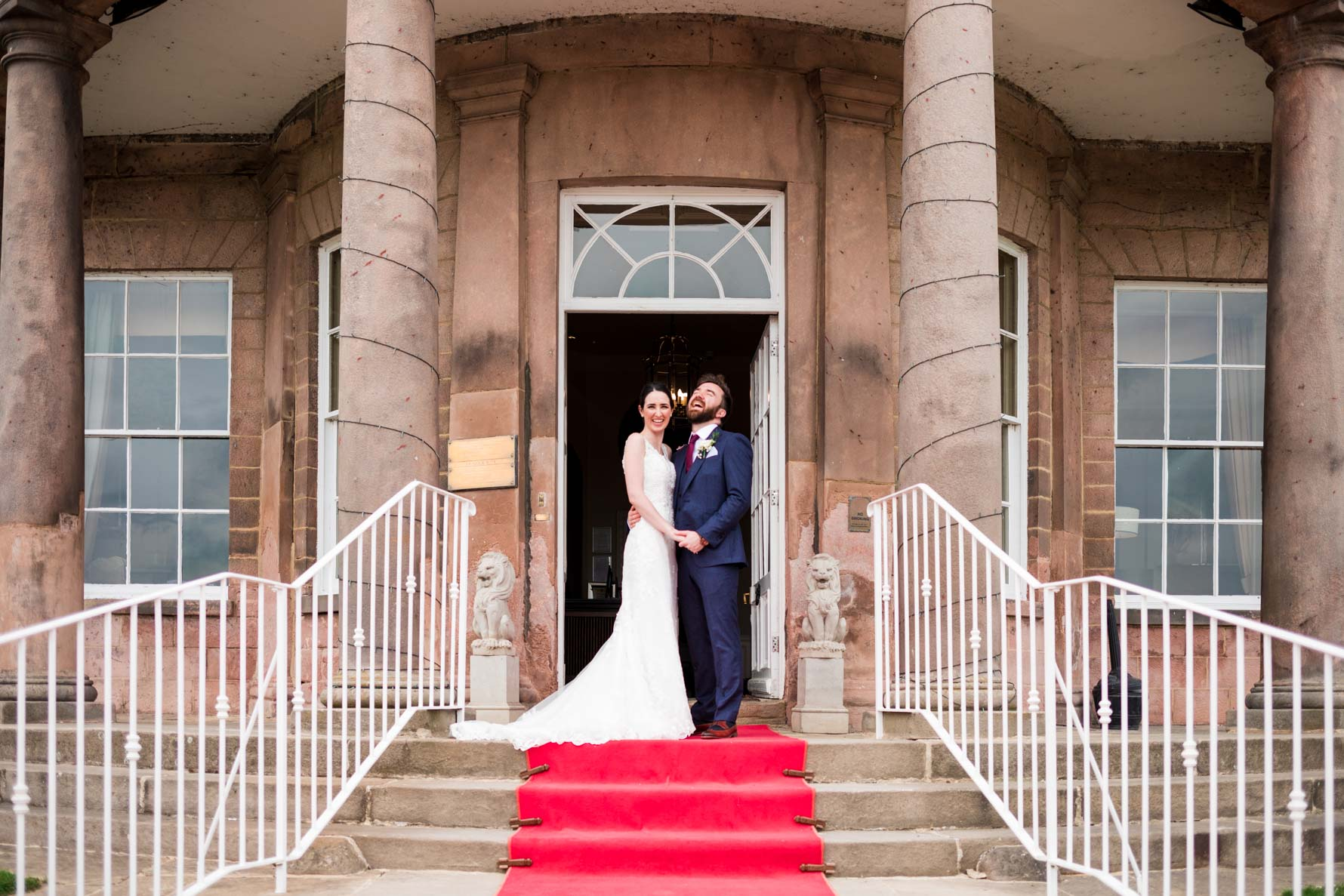 bride and groom on wood hall hotel staircase smiling