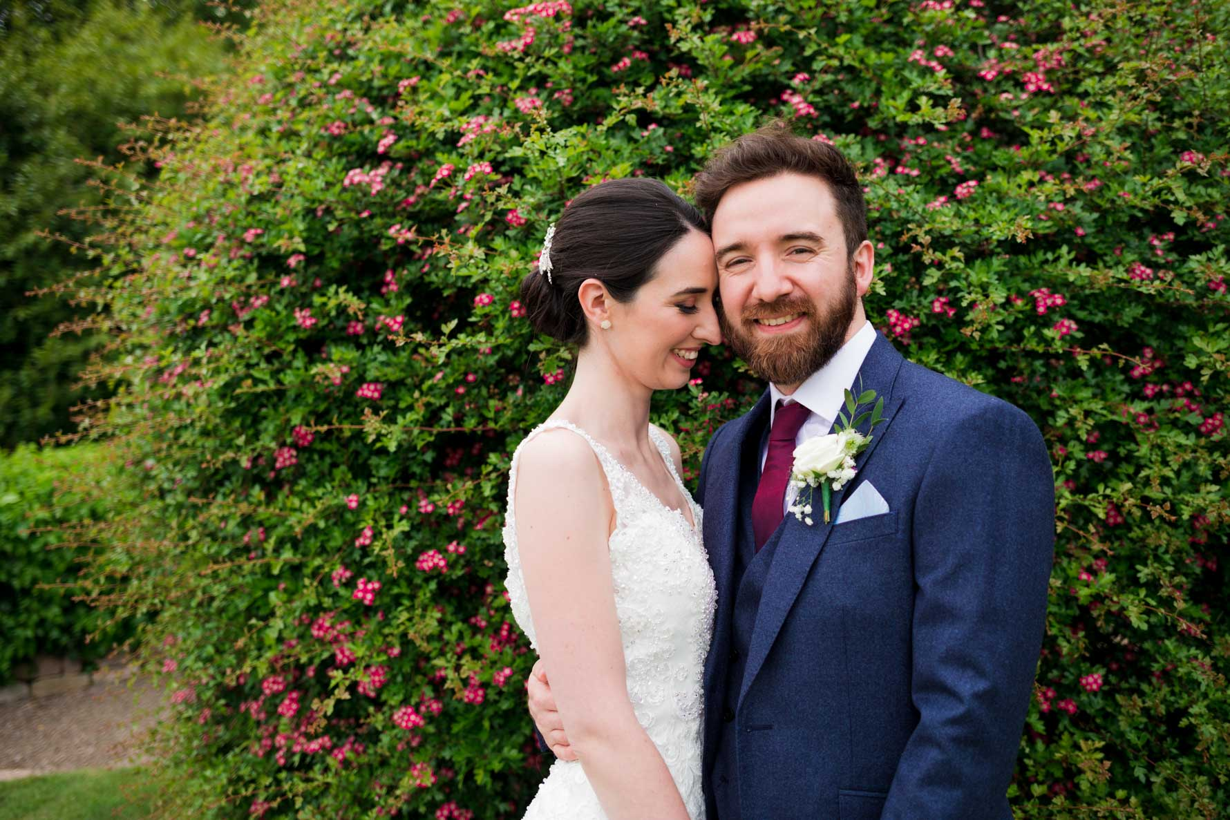 groom and bride in front of green bush with pink flowers