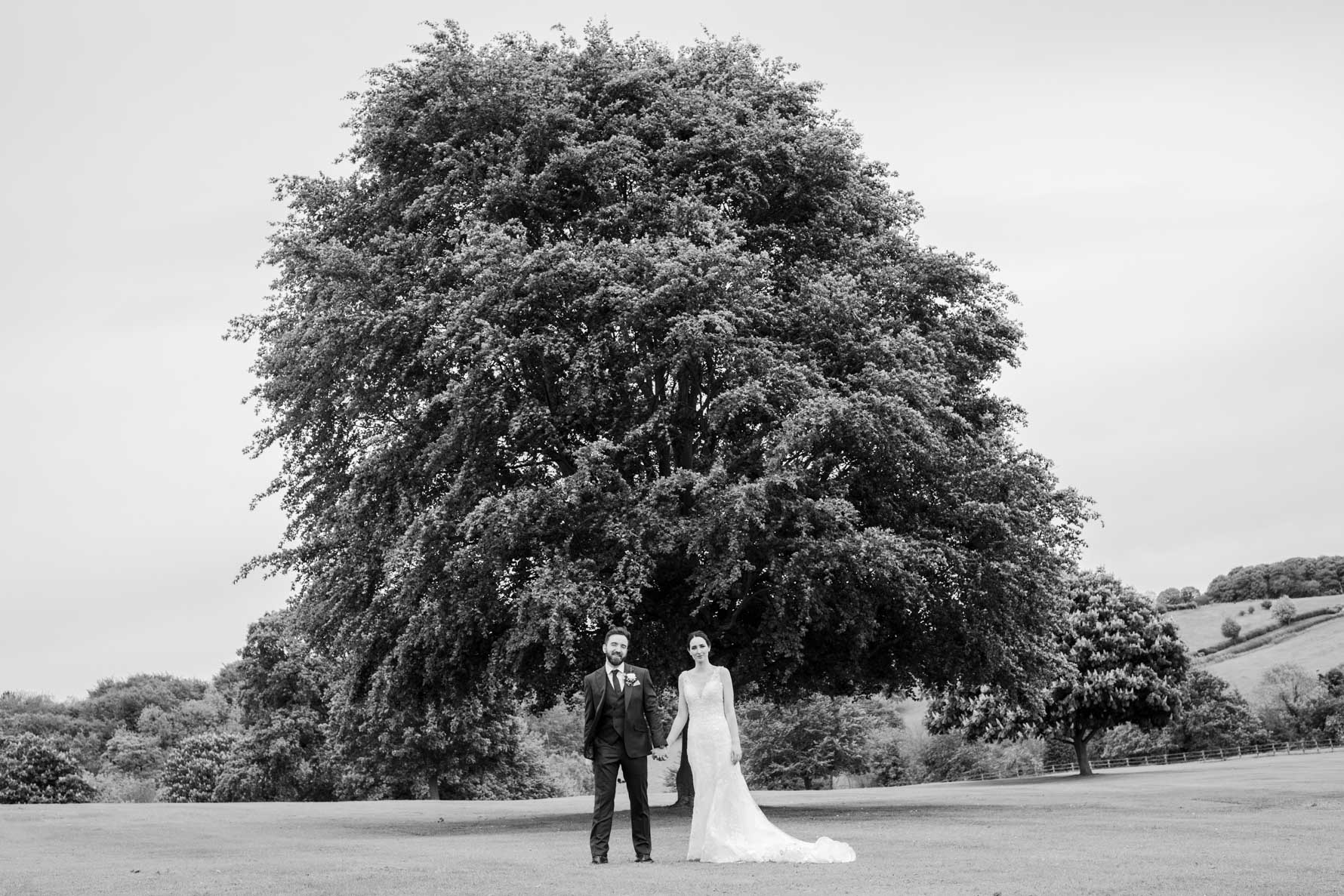 bride and groom in front of big tree in wood hall hotel grounds