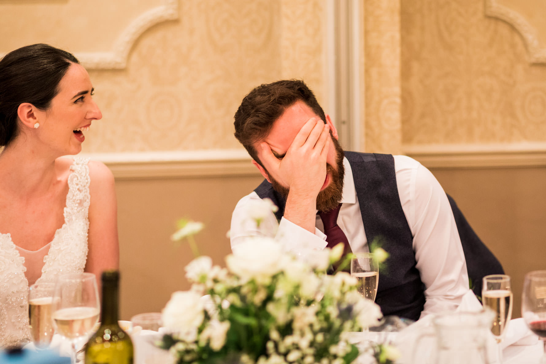 groom with hand in front of his face during best mans speech