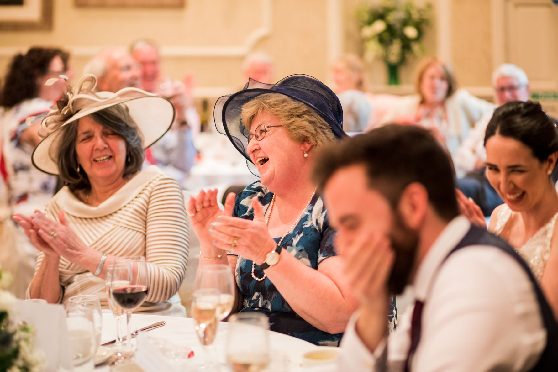 Wedding guests laughing at best man's speech