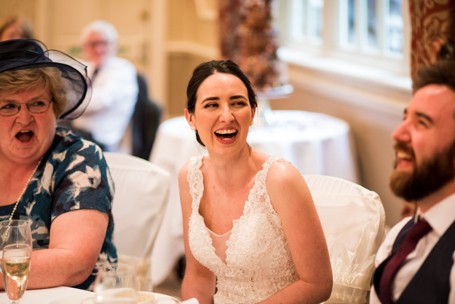 dark haired bride laughing at wood hall wedding reception