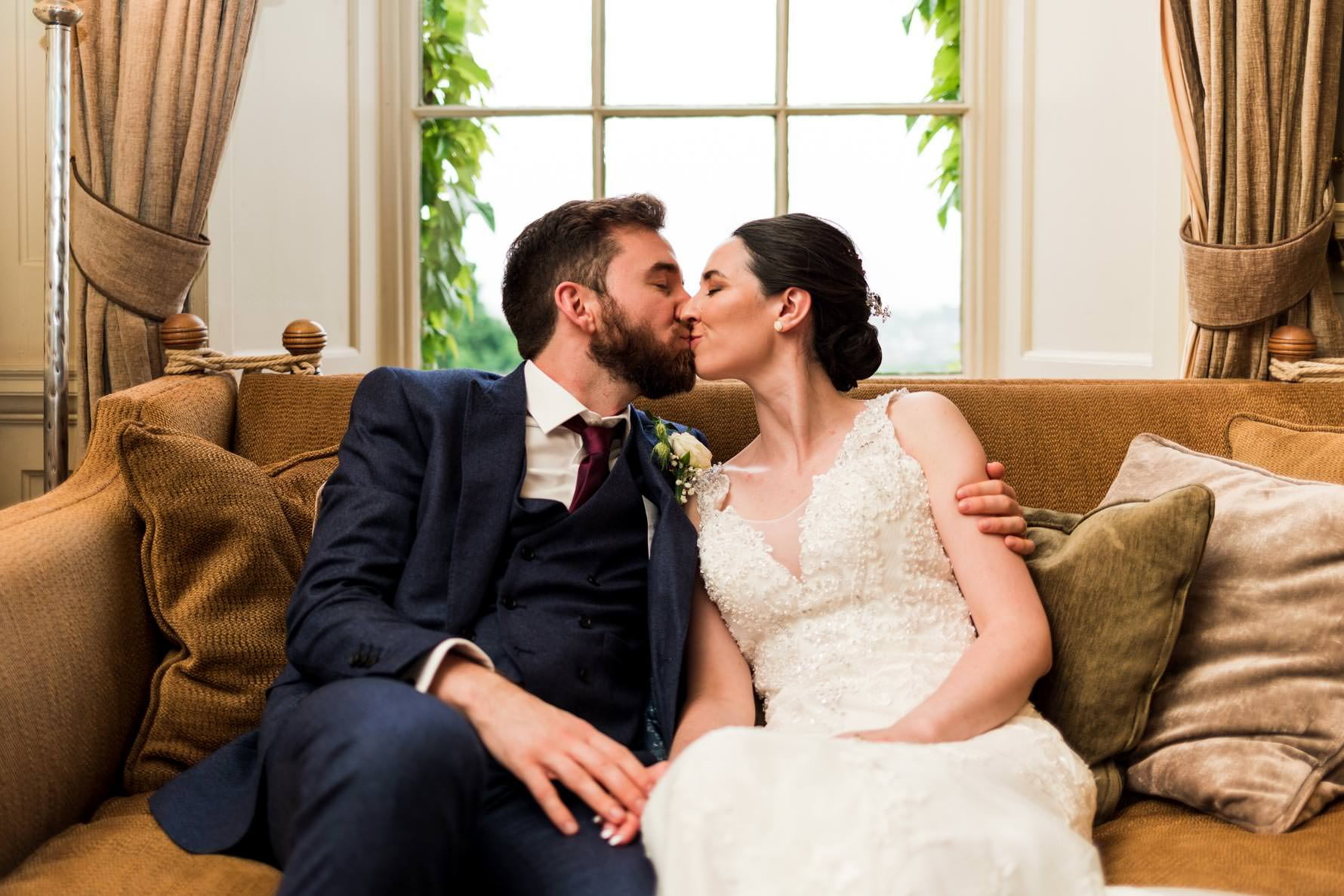 bride and groom kissing on brown sofa in front of window