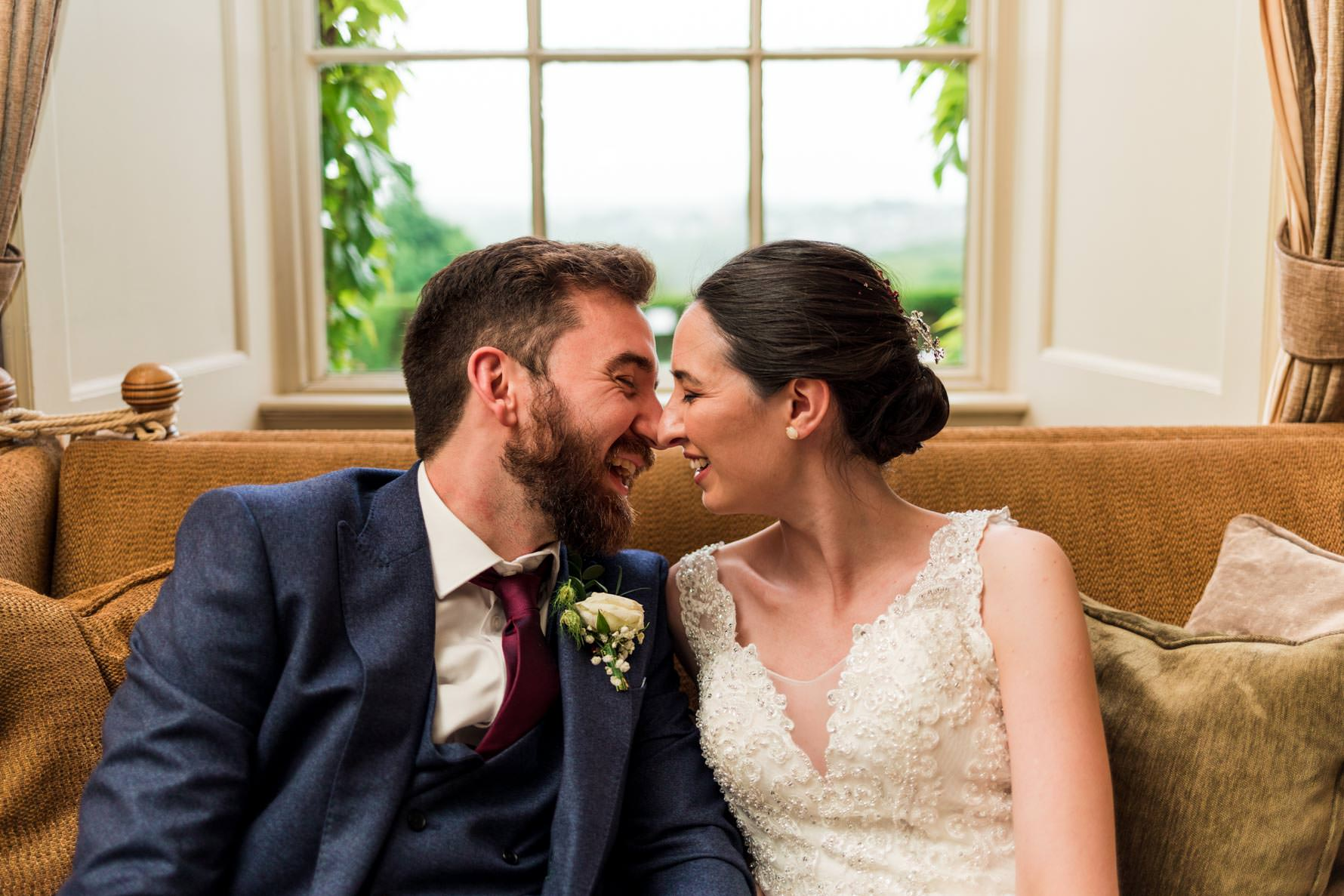 groom and bride Eskimo kiss on brown sofa in front of window