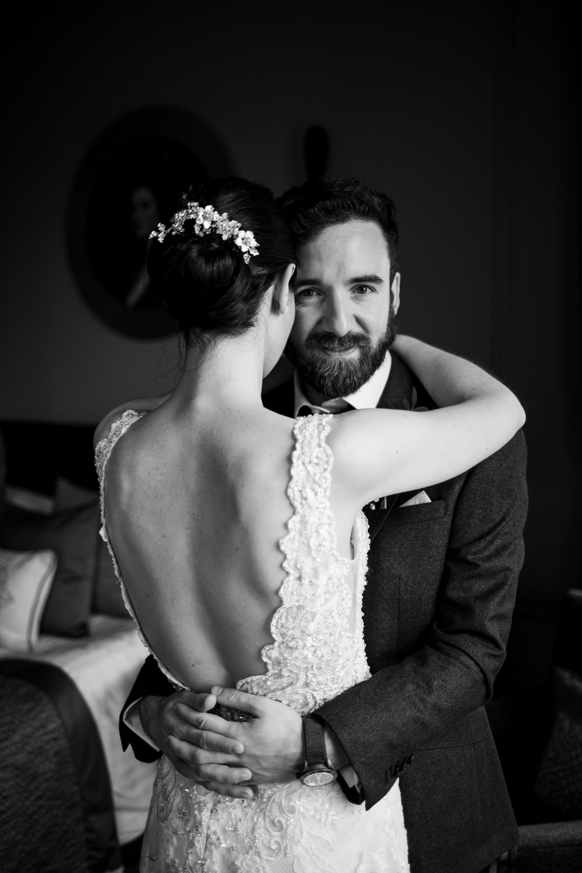 groom looking into camera whilst hugging bride with cut out lace dress