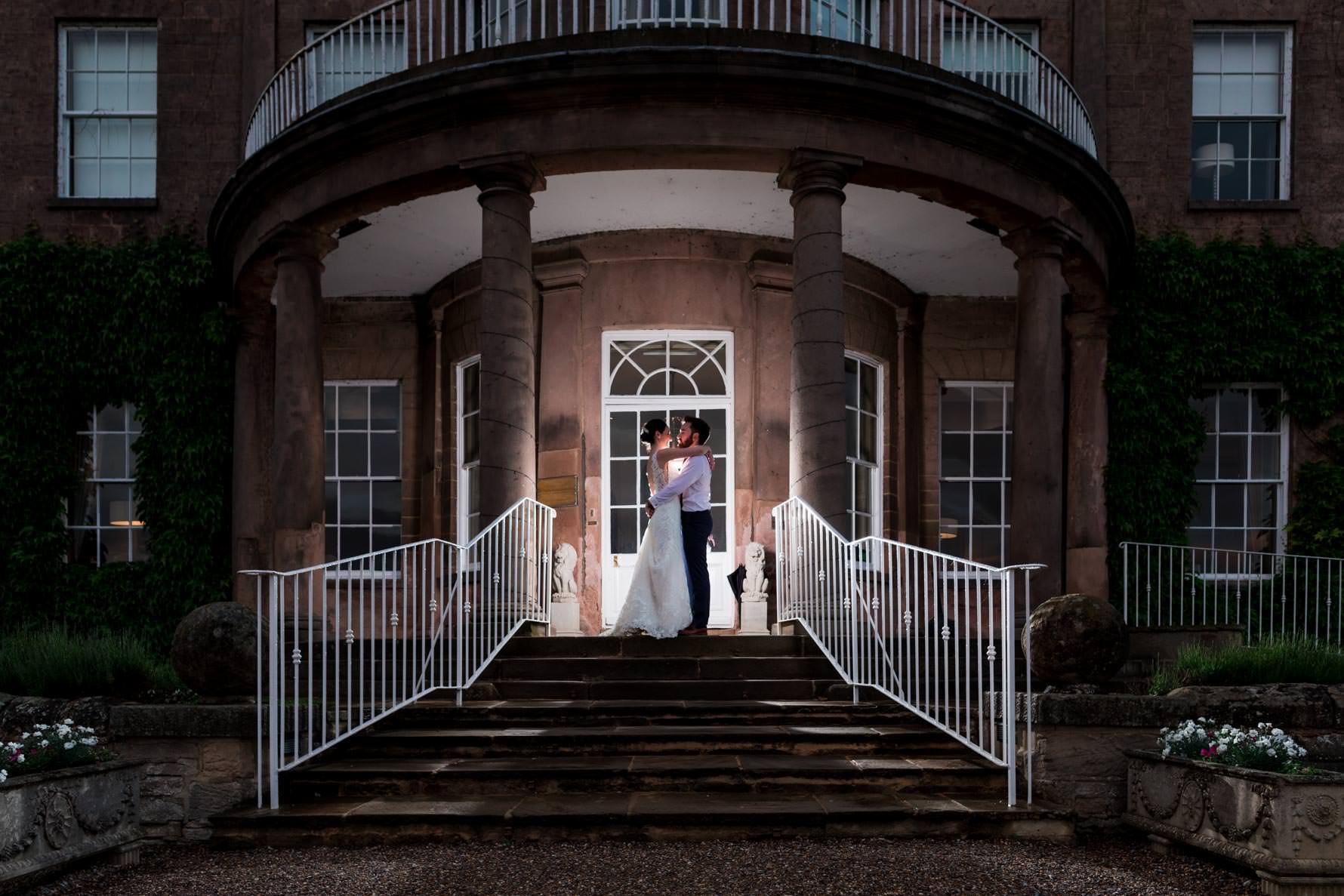 bride and groom backlight on staircase of wood hall kissing