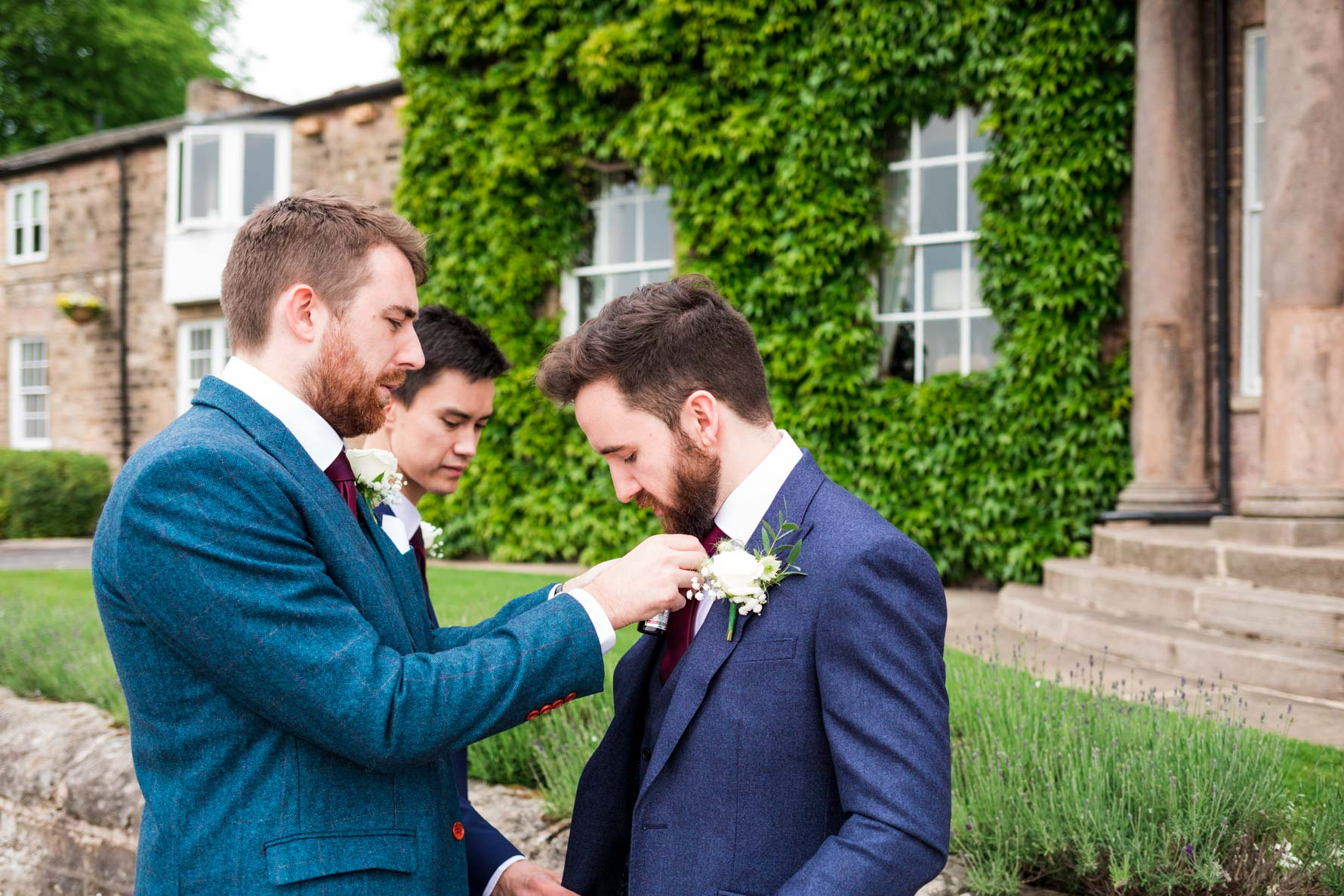 Groomsmen straightening grooms suit before ceremony