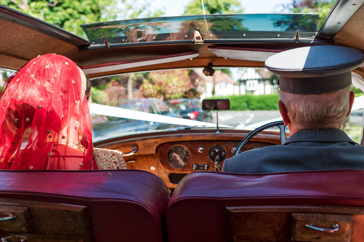 Bride with red veil sitting in Bentley next to driver