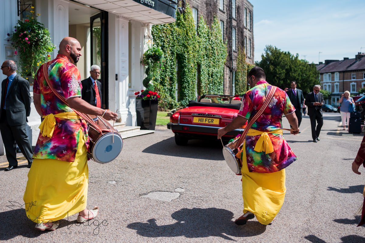Two Indian drummers in sunshine outside old swan hotel harrogate