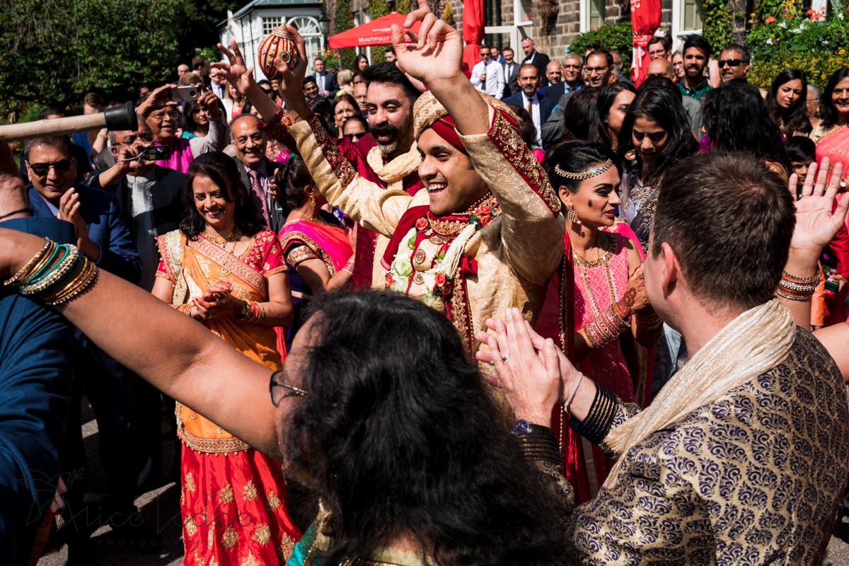 Indian groom dancing in sunshine surrounded by wedding guests