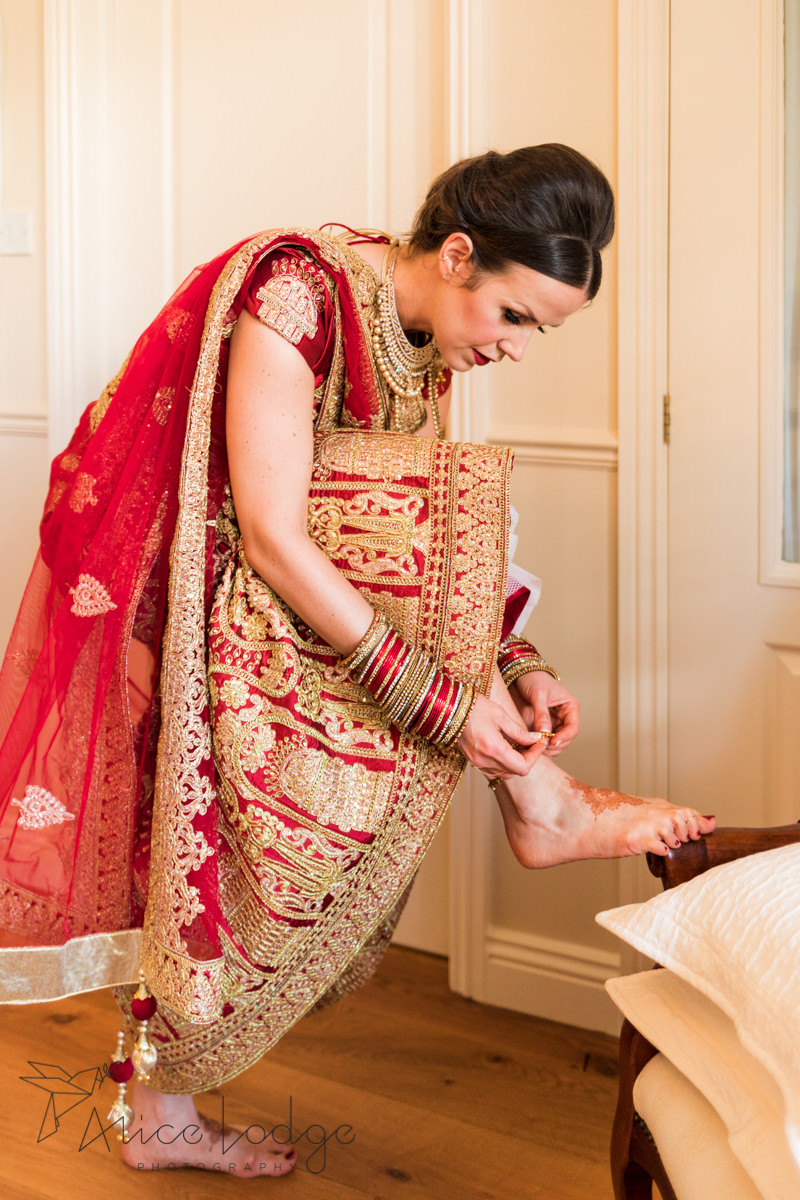 Bride in red Indian wedding Lengha putting on foot bracelet