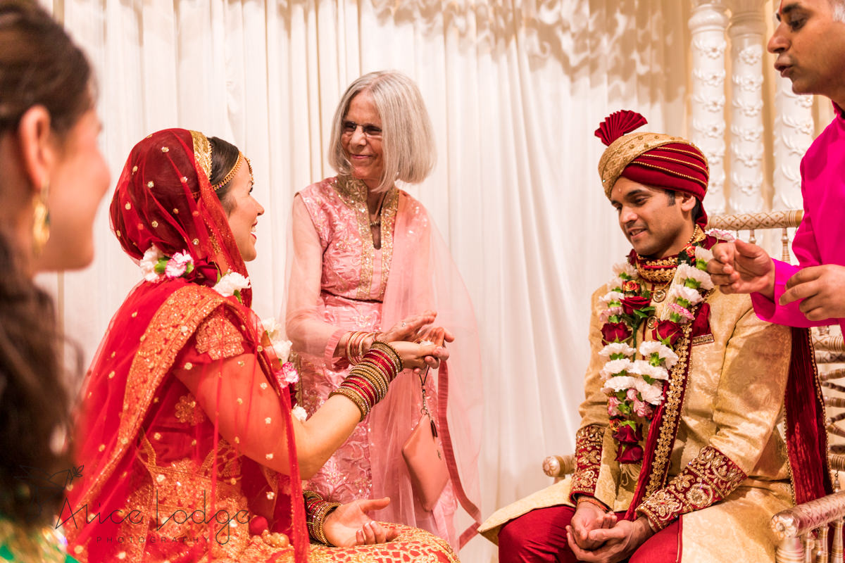 Bride and Groom with brides mother at Indian wedding ceremony