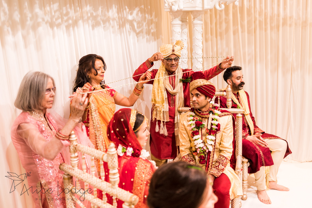 The family holding a string over bride and groom at Hindu wedding