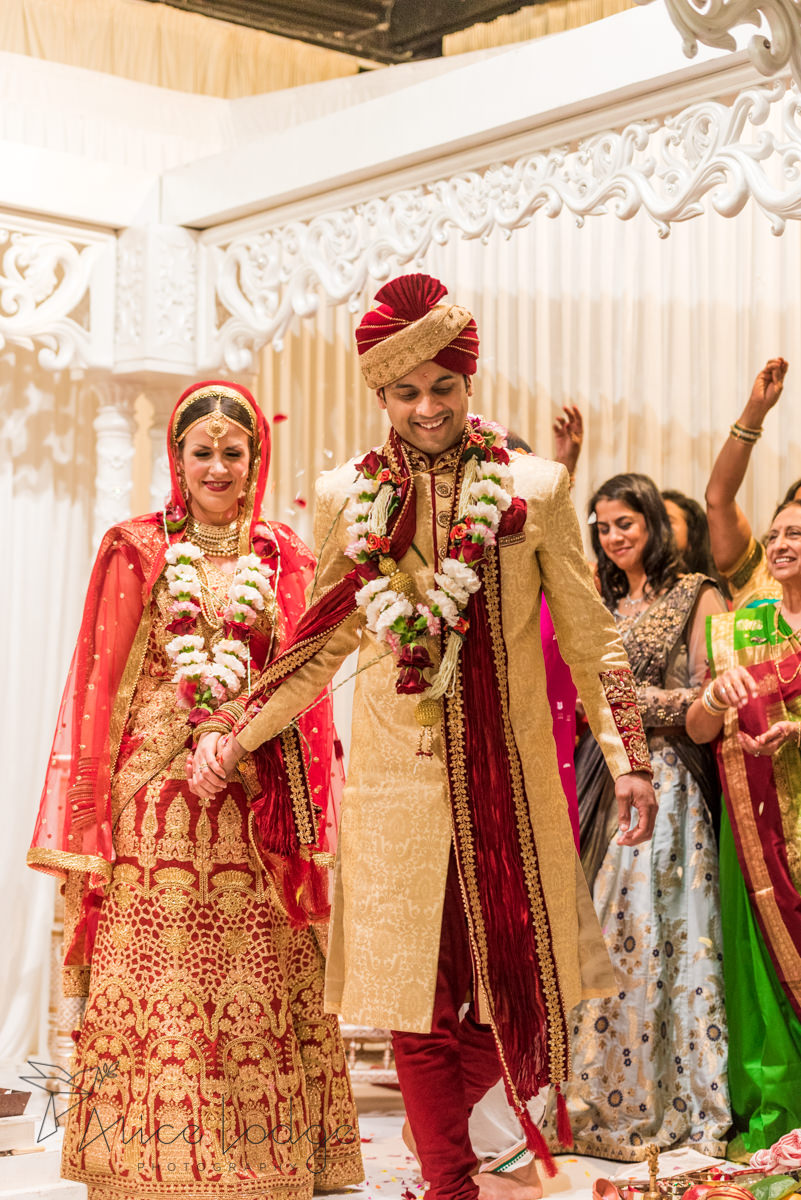 Bride and groom walking in Indian outfits whilst petals are being thrown