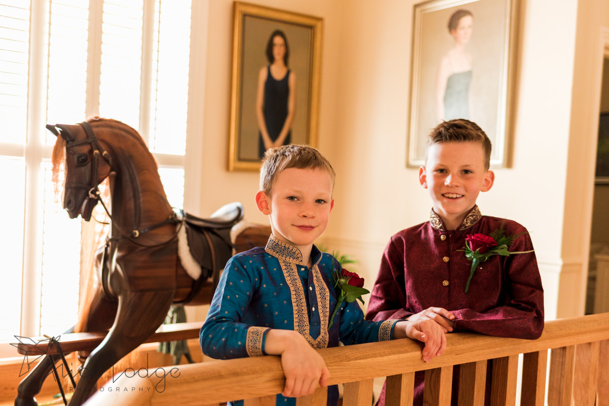 Two pageboys in Indian wedding outfits smiling on stairs landing