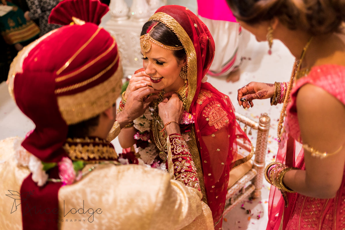 Groom putting neckless on bride during Hindu wedding ceremony