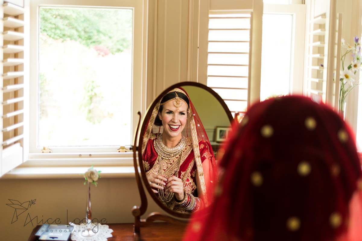 Bride in red Indian wedding outfit looking in mirror smiling