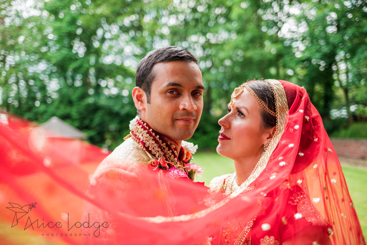 Bride with red veil looking at Indian groom