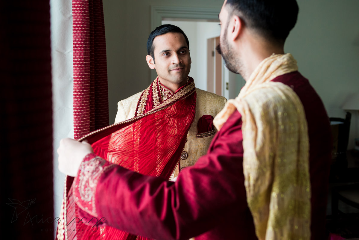 Indian groom putting on red scarf before wedding ceremony