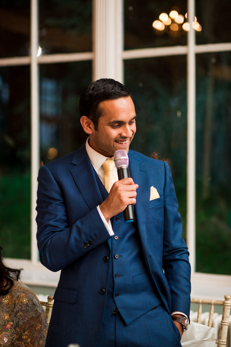 Groom in blue suit giving wedding speech