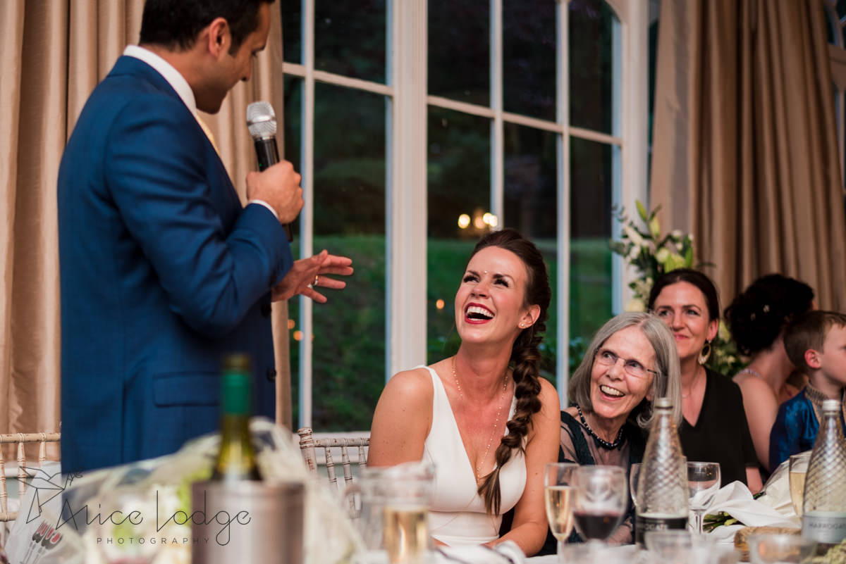 Bride smiling at groom during wedding speech