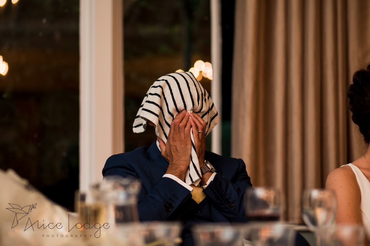 Groom hiding under towel at best man's wedding speech