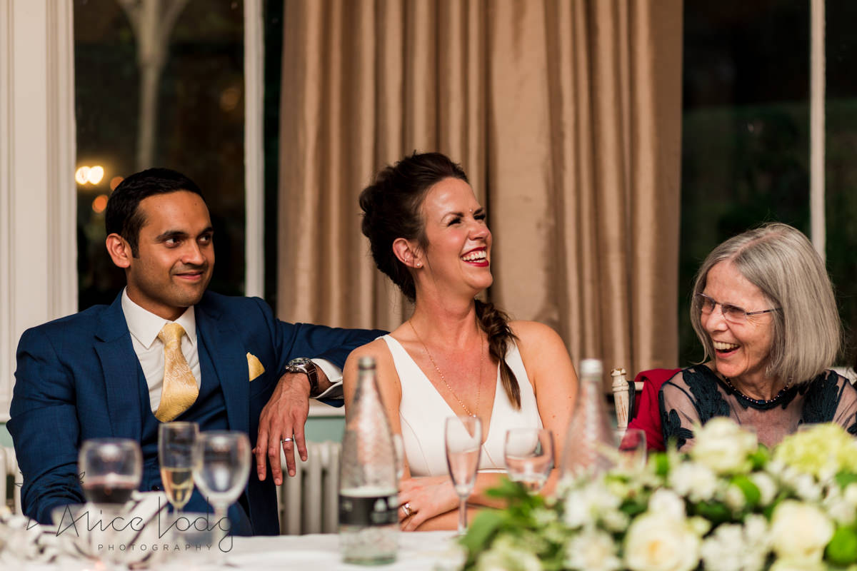 Bride and groom laughing at wedding speech