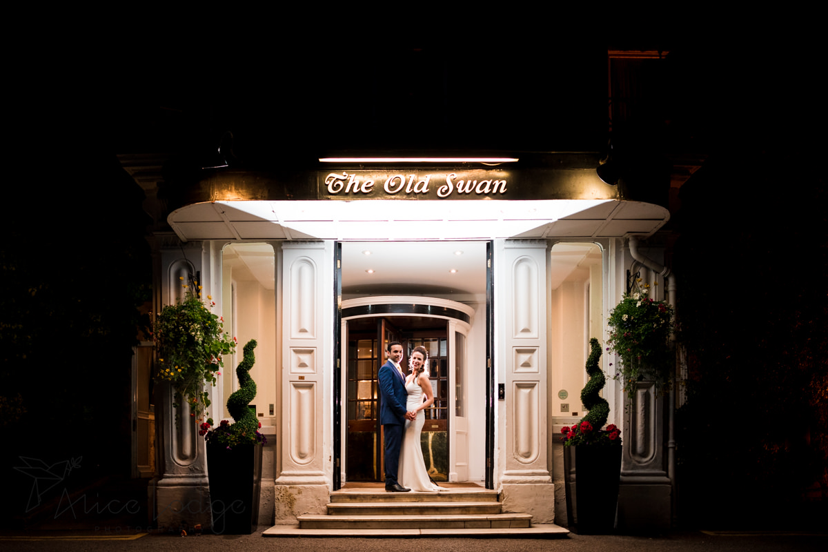 Bride and groom backlit in front of the old swan hotel harrogate