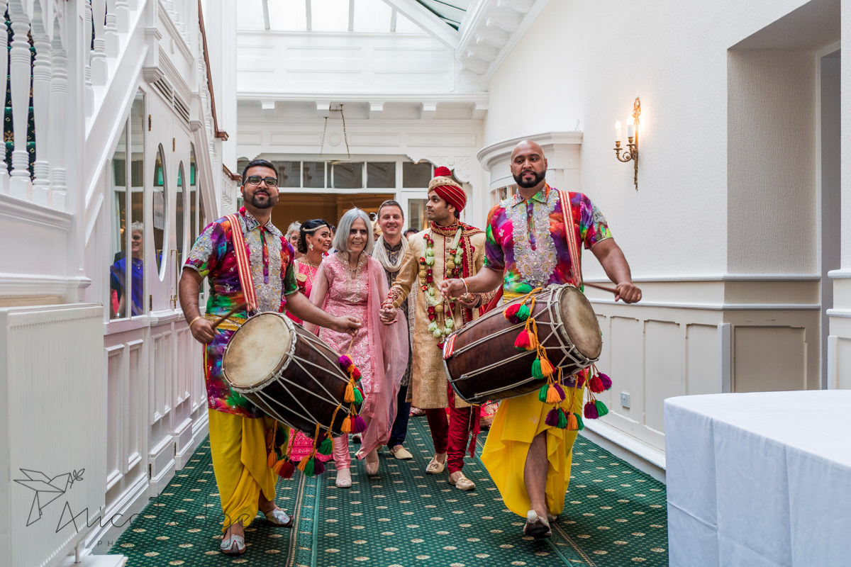 Mother of the bride with Indian groom walking through corridor at old swan hotel harrogate