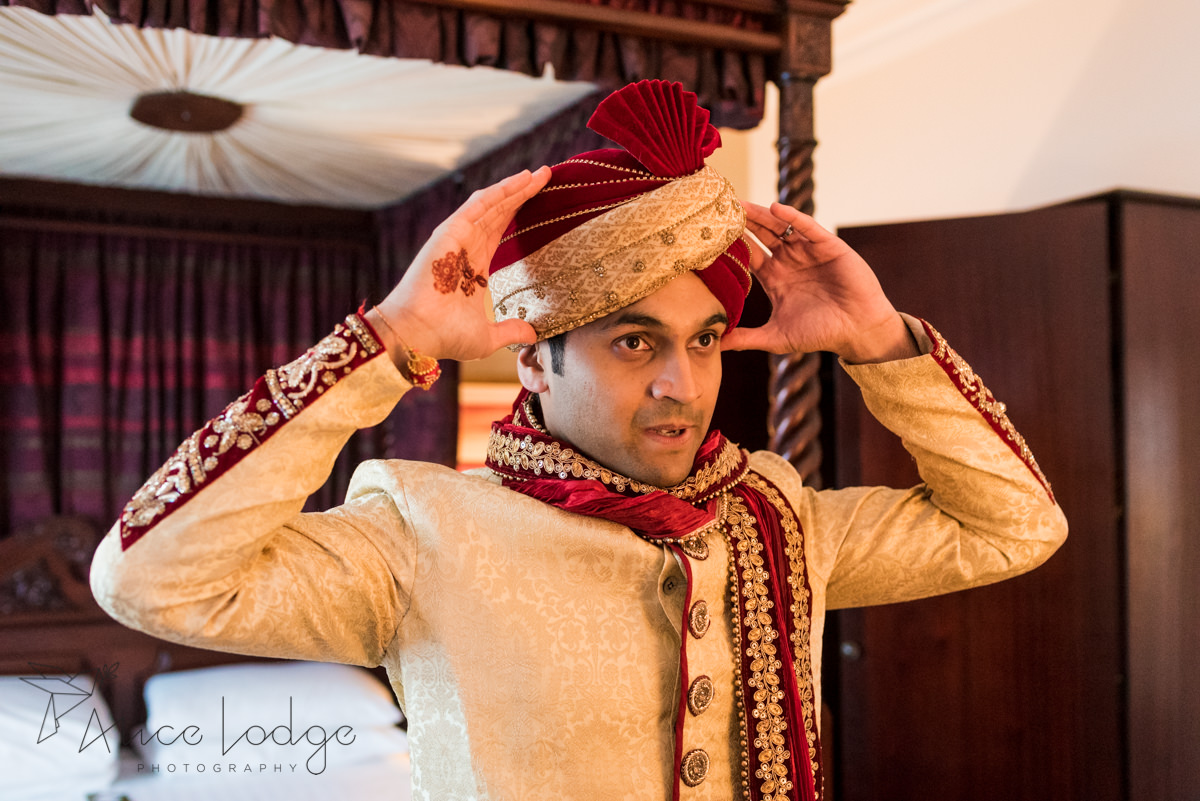 Indian groom putting on wedding turban