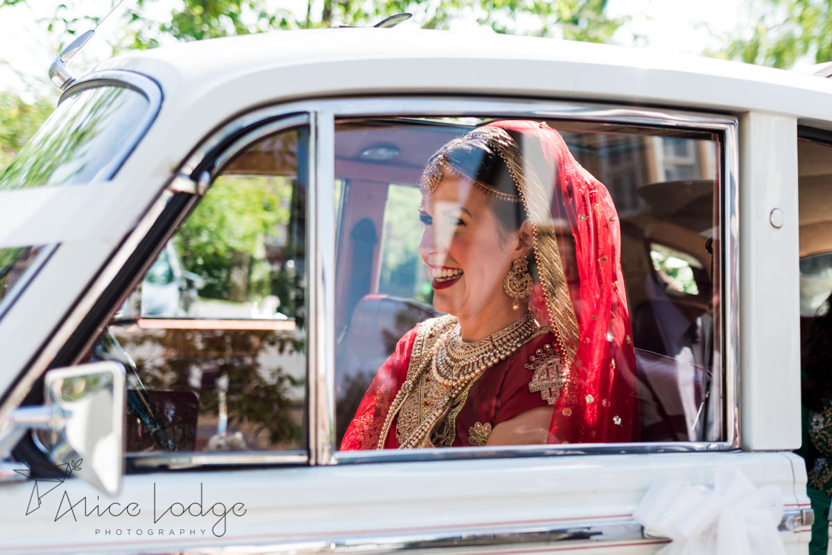 Bride in Indian outfit sitting in Bentley smiling