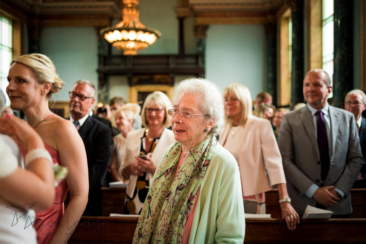 grandma in church smiling at wedding ceremony