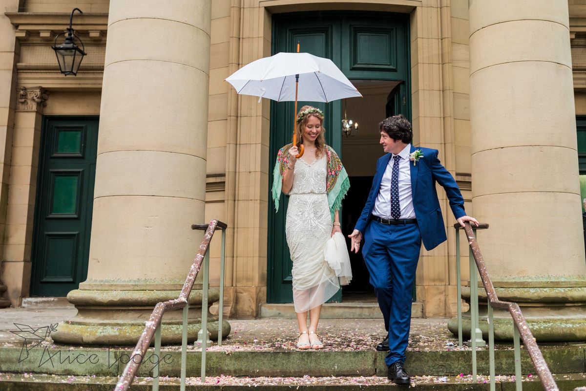 bride with umbrella and groom on church steps