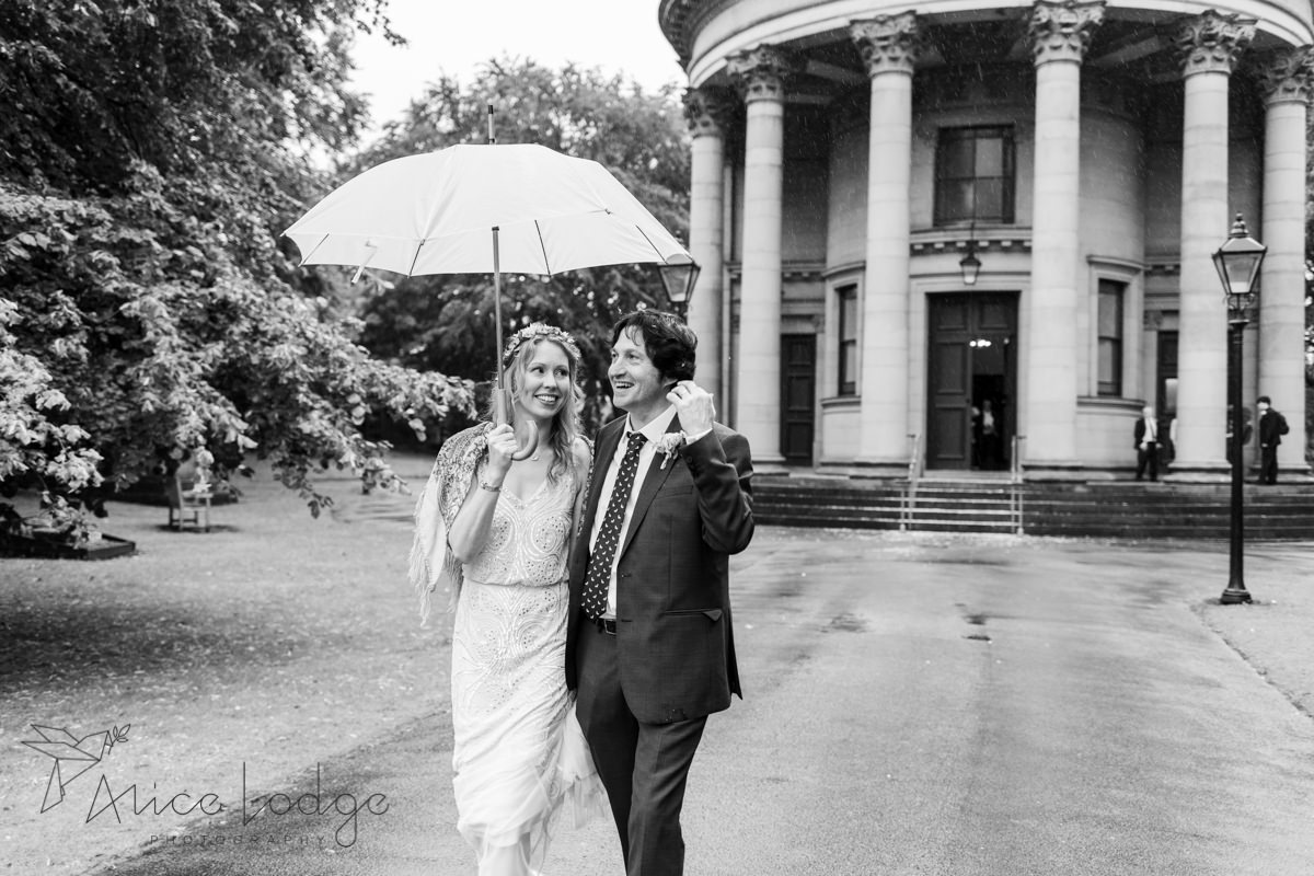 bride and groom walking in rain with white umbrella