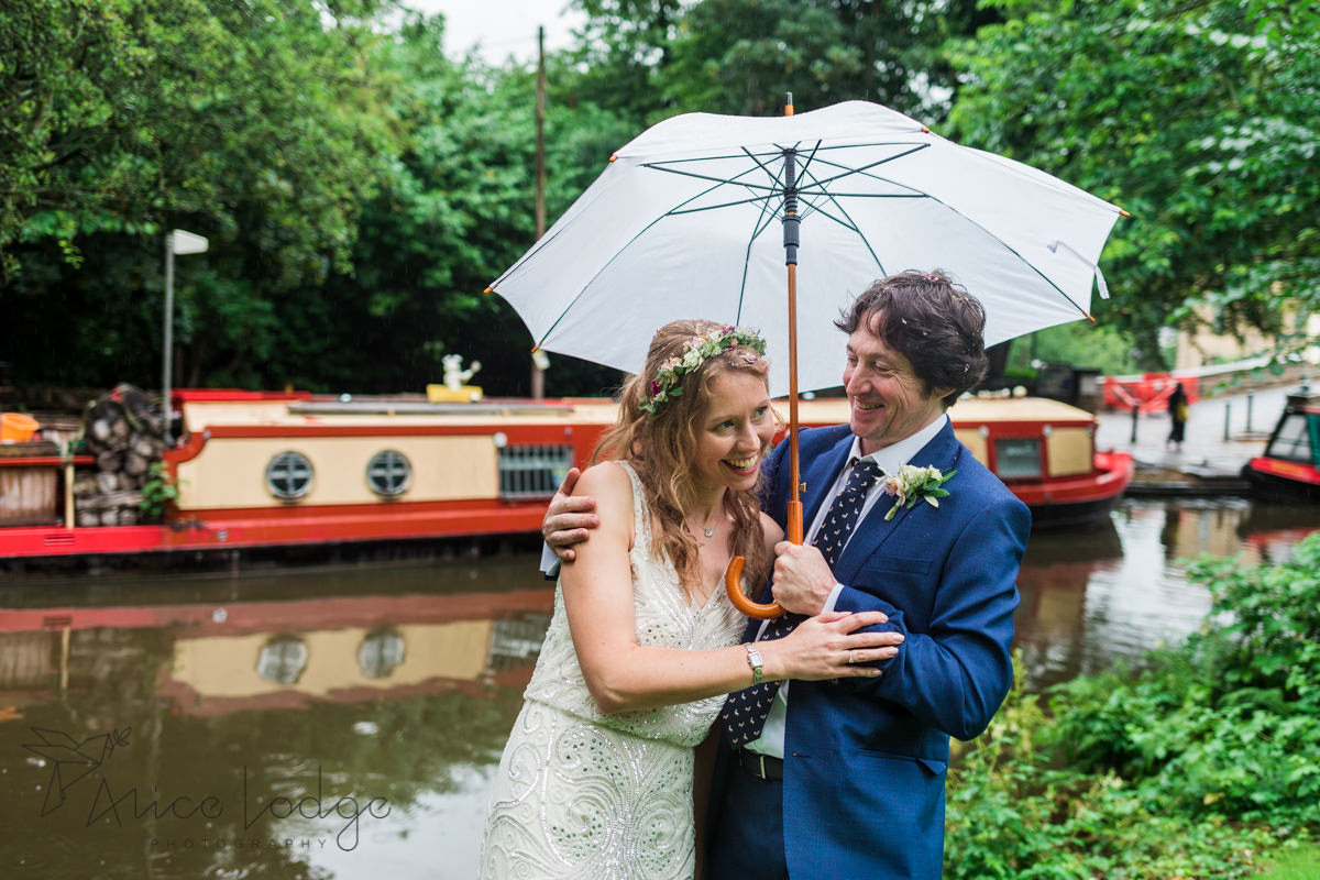 bride and groom under umbrella in front of red barge