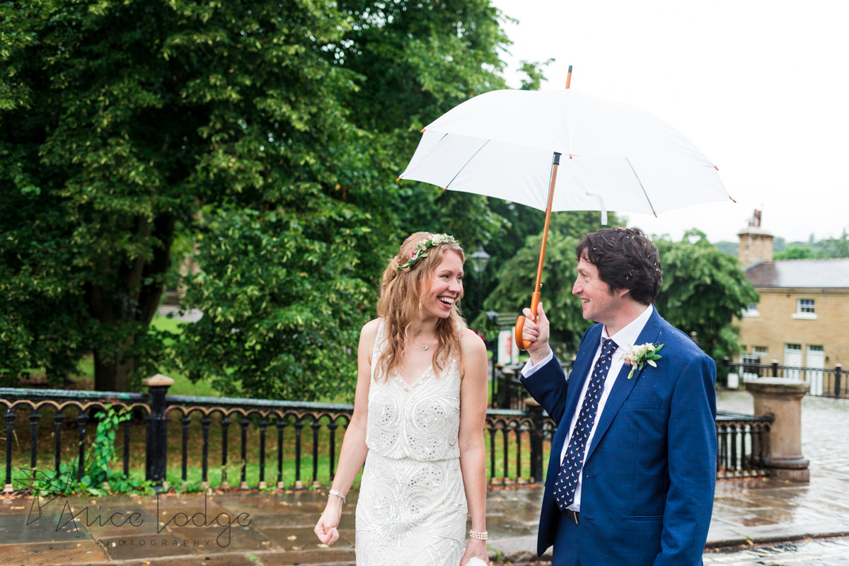 bride and groom walking under umbrella smiling at each other
