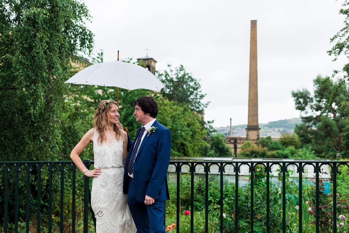 bride and groom under umbrella in front of salts mill Saltaire