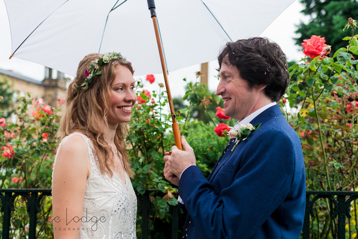 bride and groom under umbrella in front of roses