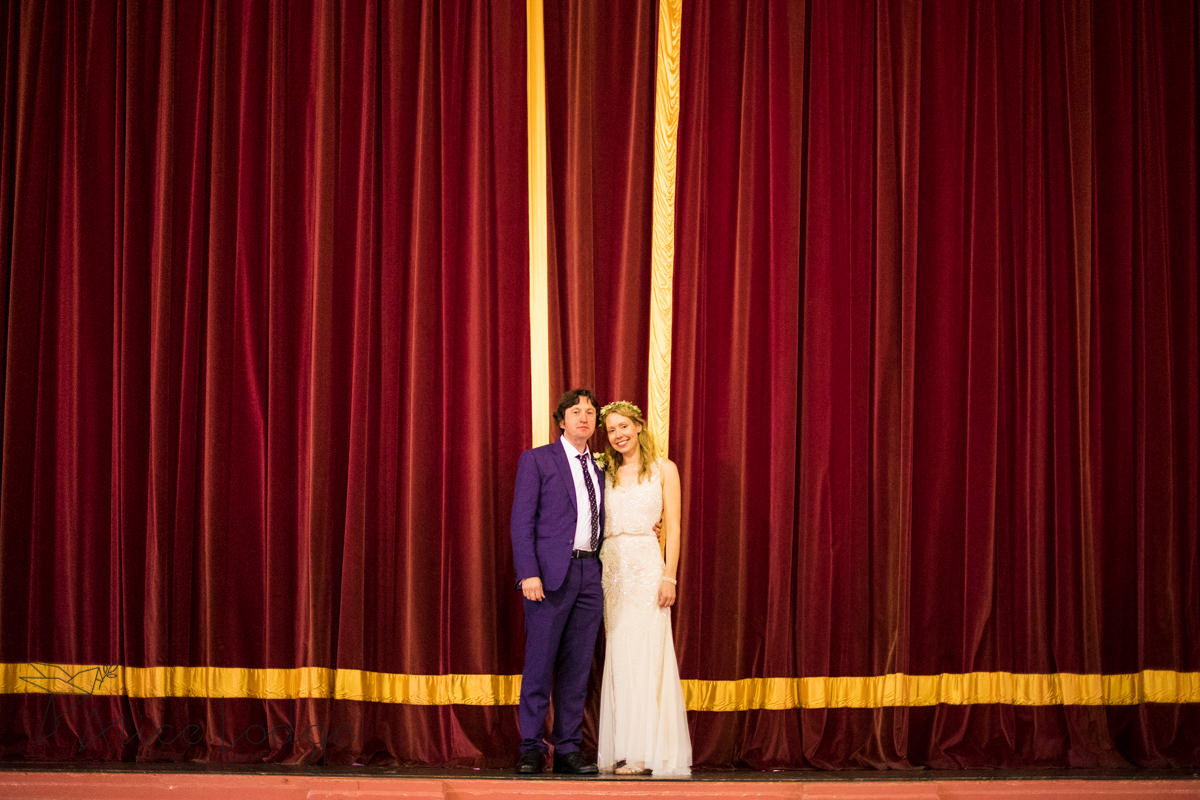 bride and groom in front of red curtain at Victoria Hall