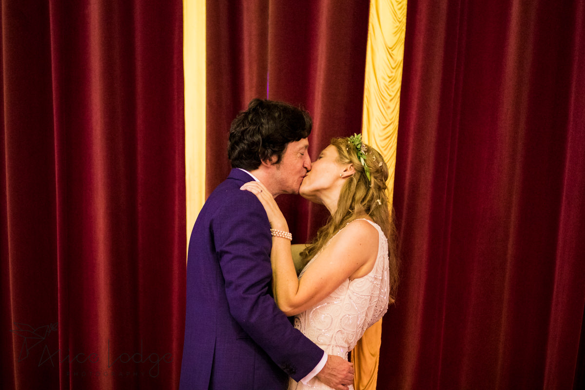 bride and groom kissing in front of red velvet curtain